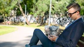 Ο επιχειρηματίας κάθεται στον πάγκο στο πάρκο και αρχίζει ένα κινητό τηλέφωνο φιλμ μικρού μήκους