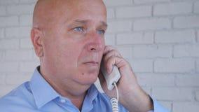 Ο επιχειρηματίας κάνει ένα τηλεφώνημα χρησιμοποιώντας τη γραμμή εδάφους γραφείων στοκ εικόνες