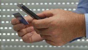 Ο επιχειρηματίας κάνει τη σε απευθείας σύνδεση πληρωμή χρησιμοποιώντας ένα κινητό τηλέφωνο και μια πιστωτική κάρτα απόθεμα βίντεο