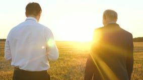 Ο επιχειρηματίας και ο αγρότης διαπραγματεύονται στο ηλιοβασίλεμα στον τομέα άτομα ομαδικής εργασίας σε ένα επιχειρησιακό πρόγραμ φιλμ μικρού μήκους