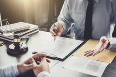 Ο επιχειρηματίας και ο αρσενικός δικηγόρος ή ο δικαστής συμβουλεύονται τη διοργάνωση της συνεδρίασης των ομάδων στοκ εικόνα