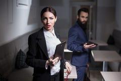 Ο επιχειρηματίας και η επιχειρηματίας έντυσαν στα κοστούμια και κράτηση του πίνακα Στοκ Φωτογραφίες