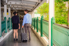 Ο επιχειρηματίας και η επιχειρηματίας μιλούν και περπατούν μαζί με τις μαύρες αποσκευές στη δημόσια οδό Στοκ Φωτογραφίες