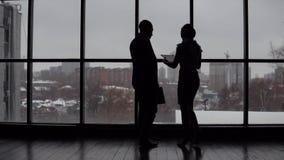 Ο επιχειρηματίας και η επιχειρησιακή γυναίκα συναντιούνται στο γραφείο κοντά στο παράθυρο και συζητούν το πρόγραμμα φιλμ μικρού μήκους