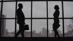 Ο επιχειρηματίας και η επιχειρησιακή γυναίκα συναντιούνται στο γραφείο κοντά στο παράθυρο και συζητούν το πρόγραμμα 4K απόθεμα βίντεο