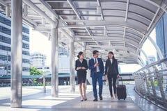 Ο επιχειρηματίας και η επιχειρηματίας περπατούν μαζί με τις αποσκευές στην πόλη, έννοια επιχειρησιακού ταξιδιού στοκ φωτογραφία με δικαίωμα ελεύθερης χρήσης