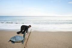 Ο επιχειρηματίας και η χελώνα είναι έτοιμοι να συναγωνιστούν στην παραλία άμμου Στοκ εικόνα με δικαίωμα ελεύθερης χρήσης