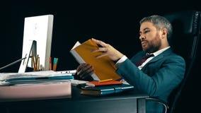 Ο επιχειρηματίας κοιτάζει μέσω των επιχειρησιακών εγγράφων στον κίτρινο φάκελλο Μαύρη ανασκόπηση 4K βίντεο απόθεμα βίντεο