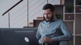 Ο επιχειρηματίας κοιτάζει στην οθόνη lap-top και αναλύει όλες τις νέες πληροφορίες από τον πόρο δικτύων χρηματοδότησης φιλμ μικρού μήκους
