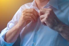 Ο επιχειρηματίας κουμπώνει το άσπρο πουκάμισο με το ρόλο επάνω στα μανίκια πιετών στοκ φωτογραφία