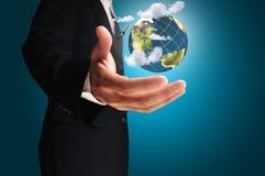 Ο επιχειρηματίας κρατά τη γη σε ένα χέρι Στοκ Φωτογραφίες