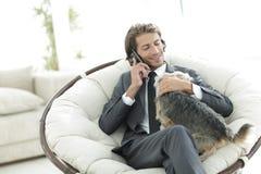Ο επιχειρηματίας κρατά το κατοικίδιο ζώο του και μιλά σε ένα smartphone Στοκ Εικόνες