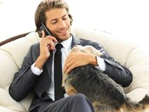 Ο επιχειρηματίας κρατά το κατοικίδιο ζώο του και μιλά σε ένα smartphone Στοκ φωτογραφία με δικαίωμα ελεύθερης χρήσης