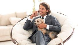 Ο επιχειρηματίας κρατά το κατοικίδιο ζώο του και μιλά στο smartphone καθμένος σε μια άνετη καρέκλα Στοκ φωτογραφίες με δικαίωμα ελεύθερης χρήσης