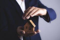 Ο επιχειρηματίας κρατά το σπίτι στοκ φωτογραφία