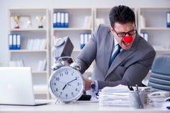 Ο επιχειρηματίας κλόουν στο γραφείο με το σφυρί και ένα ξυπνητήρι Στοκ Εικόνα