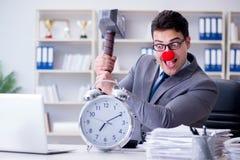 Ο επιχειρηματίας κλόουν στο γραφείο με το σφυρί και ένα ξυπνητήρι Στοκ Φωτογραφίες