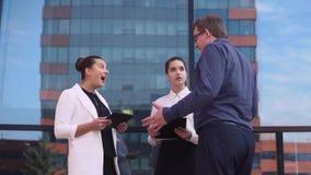 Ο επιχειρηματίας λέει τις καλές ειδήσεις σε δύο επιχειρησιακά κορίτσια και είναι ευτυχή κίνηση αργή HD απόθεμα βίντεο