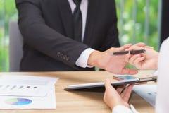 Ο επιχειρηματίας λέει το αριθ. ή τη λαβή επάνω όταν γυναίκα που δίνει τη μάνδρα για την υπογραφή Στοκ Εικόνες