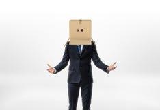 Ο επιχειρηματίας μένει τα χέρια του στις πλευρές με ένα κιβώτιο στο κεφάλι του με τις τρύπες για τα μάτια στο άσπρο υπόβαθρο Στοκ εικόνες με δικαίωμα ελεύθερης χρήσης
