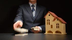Ο επιχειρηματίας μετρά χρήματα και πλησιάζει σε ένα πρότυπο σπιτιών σε έναν πίνακα Στοκ εικόνες με δικαίωμα ελεύθερης χρήσης