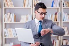 Ο επιχειρηματίας με ένα lap-top που λειτουργεί στη βιβλιοθήκη Στοκ φωτογραφίες με δικαίωμα ελεύθερης χρήσης