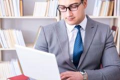 Ο επιχειρηματίας με ένα lap-top που λειτουργεί στη βιβλιοθήκη Στοκ Φωτογραφίες