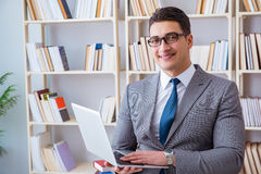 Ο επιχειρηματίας με ένα lap-top που λειτουργεί στη βιβλιοθήκη Στοκ εικόνα με δικαίωμα ελεύθερης χρήσης