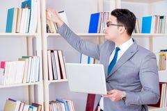 Ο επιχειρηματίας με ένα lap-top που λειτουργεί στη βιβλιοθήκη Στοκ Εικόνες