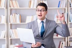 Ο επιχειρηματίας με ένα lap-top που λειτουργεί στη βιβλιοθήκη Στοκ εικόνες με δικαίωμα ελεύθερης χρήσης