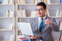 Ο επιχειρηματίας με ένα lap-top που λειτουργεί στη βιβλιοθήκη Στοκ φωτογραφία με δικαίωμα ελεύθερης χρήσης
