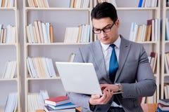 Ο επιχειρηματίας με ένα lap-top που λειτουργεί στη βιβλιοθήκη Στοκ Φωτογραφία