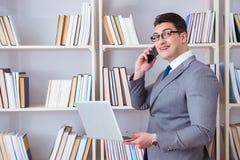 Ο επιχειρηματίας με ένα lap-top που μιλά στο τηλέφωνο που λειτουργεί στη βιβλιοθήκη Στοκ εικόνα με δικαίωμα ελεύθερης χρήσης