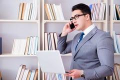 Ο επιχειρηματίας με ένα lap-top που μιλά στο τηλέφωνο που λειτουργεί στη βιβλιοθήκη Στοκ Φωτογραφίες