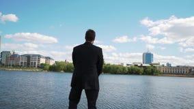 Ο επιχειρηματίας με γενναίο χαίρεται και τυχερός και τυχερός κερδίστε Φαίνεται ακμάζων στο κοστούμι και το δεσμό υπαίθριους σύγχρ απόθεμα βίντεο