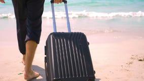 Ο επιχειρηματίας με μια βαλίτσα πηγαίνει σε μια άσπρη αμμώδη παραλία έννοια, διακοπές στοκ εικόνες