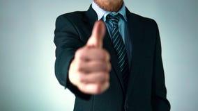 Ο επιχειρηματίας με μια γενειάδα σε ένα κοστούμι παρουσιάζει όπως, σε αργή κίνηση, καλή εργασία φιλμ μικρού μήκους