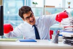 Ο επιχειρηματίας με τα εγκιβωτίζοντας γάντια στο γραφείο στοκ φωτογραφίες