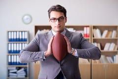 Ο επιχειρηματίας με το αμερικανικό ποδόσφαιρο στην αρχή Στοκ φωτογραφία με δικαίωμα ελεύθερης χρήσης