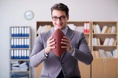 Ο επιχειρηματίας με το αμερικανικό ποδόσφαιρο στην αρχή Στοκ Φωτογραφία