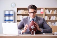 Ο επιχειρηματίας με το αμερικανικό ποδόσφαιρο στην αρχή Στοκ Εικόνα