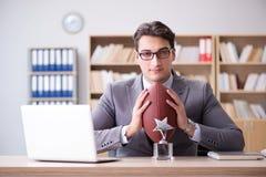 Ο επιχειρηματίας με το αμερικανικό ποδόσφαιρο στην αρχή Στοκ φωτογραφίες με δικαίωμα ελεύθερης χρήσης