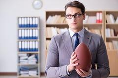 Ο επιχειρηματίας με το αμερικανικό ποδόσφαιρο στην αρχή Στοκ Φωτογραφίες