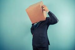 Ο επιχειρηματίας με το κιβώτιο στο κεφάλι είναι ταραγμένος Στοκ Εικόνα