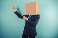 Ο επιχειρηματίας με το κιβώτιο στο κεφάλι δείχνει Στοκ Εικόνες