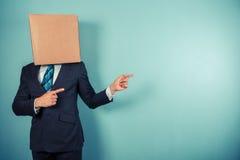 Ο επιχειρηματίας με το κιβώτιο στο κεφάλι δείχνει Στοκ Φωτογραφίες