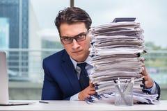 Ο επιχειρηματίας με το σωρό σωρών της γραφικής εργασίας εγγράφου στο γραφείο Στοκ Εικόνες