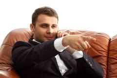 Ο επιχειρηματίας με το τηλέφωνο παρουσιάζει ένα δάχτυλο μπροστινό Στοκ Φωτογραφία