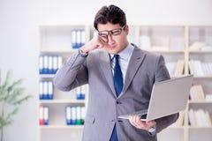 Ο επιχειρηματίας με το lap-top στο γραφείο Στοκ Εικόνες