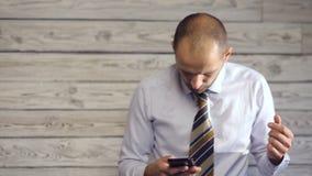 Ο επιχειρηματίας με το smartphone απολαμβάνει τις κακές ειδήσεις φιλμ μικρού μήκους